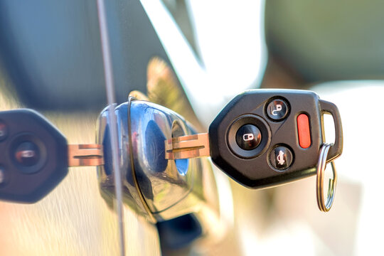 Close up of car door with key sticking out of the lock. Concept of process opening or closing vehicle.