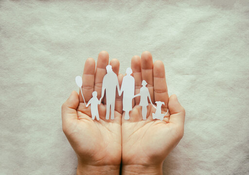 Hand holding family paper cut on fabric background. Family day concept, foster care, domestic violence, homeschool, international day of families, world mental health day, world autism awareness day.