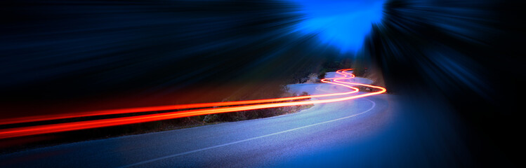 Cars light trails at night in a curve mountains road, panorama