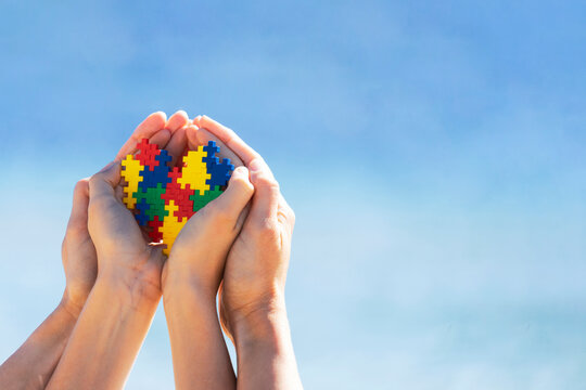 Autistic kid hands with multicolored puzzle heart supported by mother hands over blue sky background. World autism awareness day