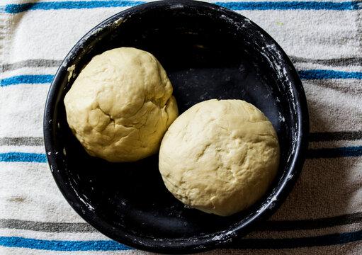 Masa de pan, en un plato negro, lista para amasar.