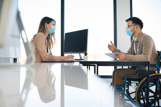 Businessman in wheelchair having a meeting with woman office