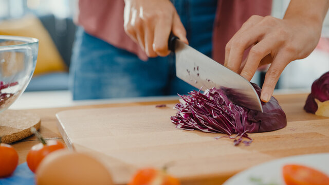 Hand of young Asian woman chef hold knife cutting Red Chinese cabbage on wooden board on kitchen table in house. Cooking vegetable salad, Lifestyle healthy food eating and traditional natural concept.