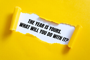 Motivational quote The year is yours. What will you do with it? appearing behind torn yellow paper.