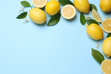 Many fresh ripe lemons with green leaves and flowers on light blue background, flat lay. Space for text
