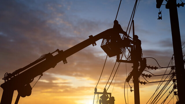 silhouette electrician working on poles to install high-voltage equipment.