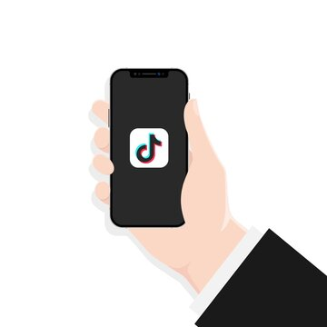 Hand holds iphone with Tik Tok app on the screen. Social media concept. UI UX white user interface. Kiev, Ukraine - March 30, 2021