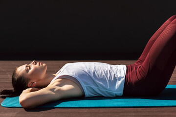 Side view of a young woman resting on the map after stretching exercises outdoors. Fitness female relaxing outside on a sunny day after training outside.