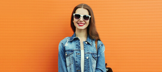 Portrait of happy smiling young woman wearing a denim jacket with backpack on a orange background