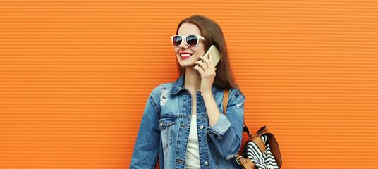 Portrait close up of smiling young woman calling on a smartphone wearing a denim jacket on an...