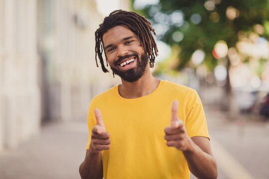 Photo portrait of young man in yellow t-shirt smiling wearing dreadlocks showing fingers choosing you smiling