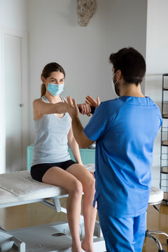 Young woman in face mask sitting on a stretcher holds dumbbell with one hand while physiotherapist helps her with rehabilitation after injuries. Treatment and restoration lost motor functions.