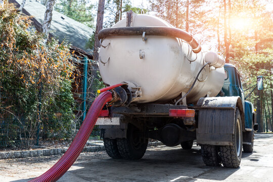 Close-up pipe hose of sewage truck car engine emptying home sewerage tank. Septic cleaning vacuum service and maintenance suburban countryside home. Suction vehicle cleaner machine pumping drainage