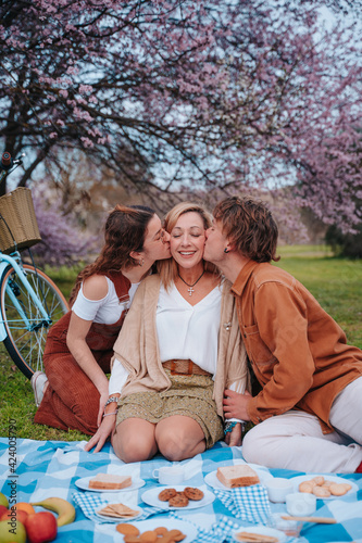 Family picnic celebrating Mother's Day with their son and daughter kissing their mother, while they enjoy a sunny day eating healthy food next to an almond tree.