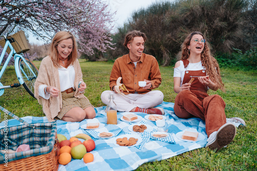Family picnic celebrating Mother's Day with their son and daughter, while they enjoy a sunny day eating healthy food next to an almond tree.