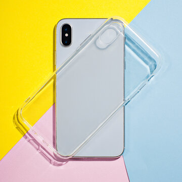 iPhone X clear case mockup, smart phone back view on the background of colored paper, blue, pink, yellow