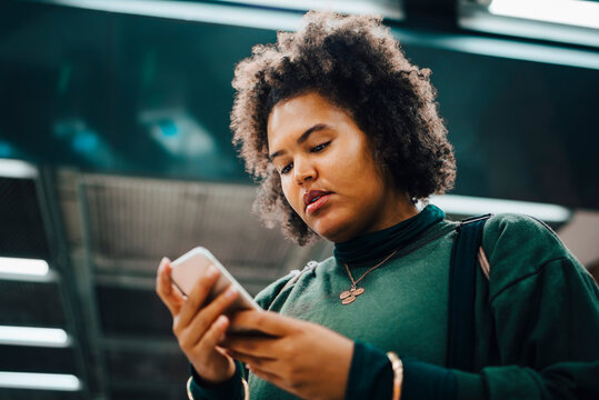 Female student text messaging on smart phone at subway