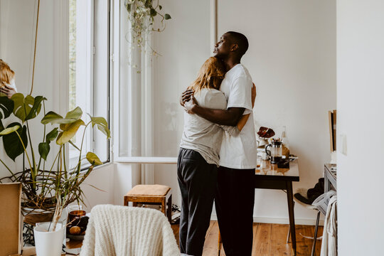 Mother embracing son while standing in living room at home