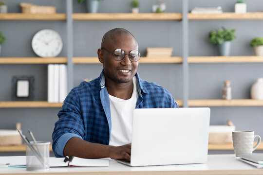 Freelance career. African american man working on laptop computer, doing new project, sitting at home workplace