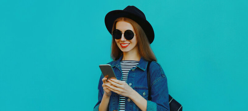 Portrait close up of smiling young woman with phone wearing a black round hat, denim jacket on a blue background