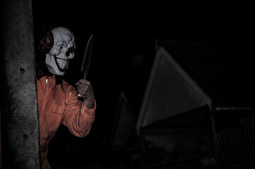 Asian handsome man wear clown mask with weapon at the night scene,Halloween festival concept,Horror scary photo of a killer in orange cloth - fototapety na wymiar