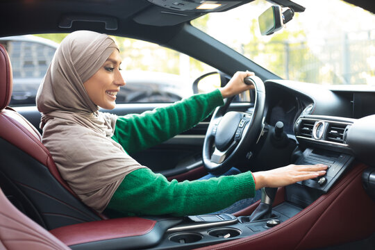 Cheerful muslim woman driving car, turning on music