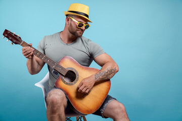 Portrait of the musician who is playing acoustic guitar and sing