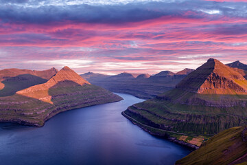 Incredible purple sunset over majestic fjords of Funningur