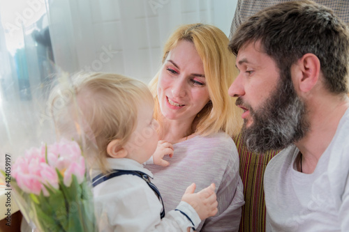 Dad with children congratulate mom on the holiday, mother's day.