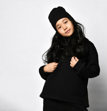 cute korean girl in a black hat and a dark warm sweater, with curls looks at the camera