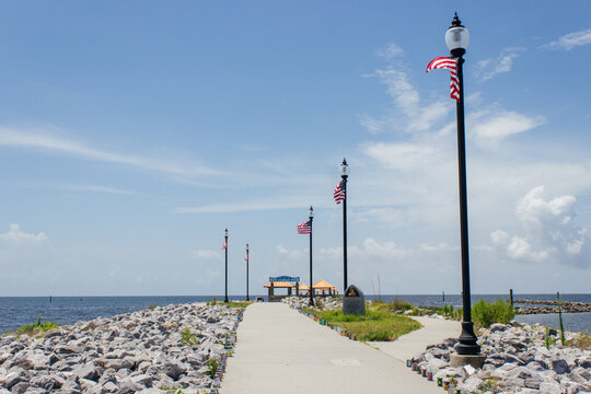 Seascape. A wooden pier with orange-roofed gazebos and American flags hanging from poles on a sunny summer day. Summer background. Ken Combs Pier, Gulfport, Massachusetts, USA