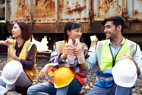 Engineers or Rail transport workers are drinking water outdoors.