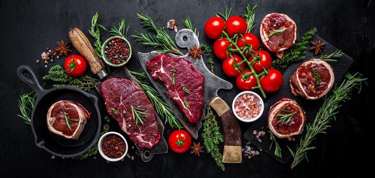 Variety of raw black angus prime meat steaks beef rump steak, Tenderloin fillet mignon or grilling with seasoning on black background. banner, menu recipe top view