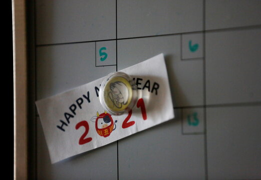 """A """"Happy New Year"""" message is stuck to a calendar in the room of Sakaguchi as her daughter visits at Nikkei Manor, an assisted living facility in Seattle"""