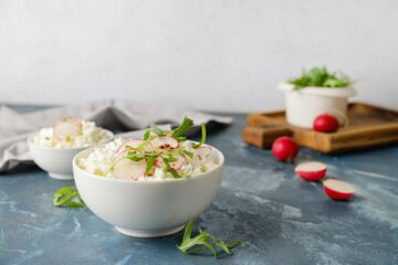 Bowls with cottage cheese on color background