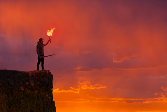 Concept of confidence - Man on a cliff with a torch and sword