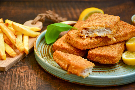 Close up of   crispy breaded  deep fried alaska pollock  fillets  with breadcrumbs served with remoulade sauce french fries  and   fresh lemon