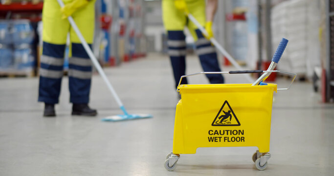 Cropped shot of worker swearing safety overall holding mop cleaning floor in warehouse