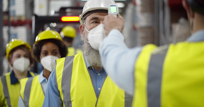 Group of workers with face mask in warehouse having temperature measurement