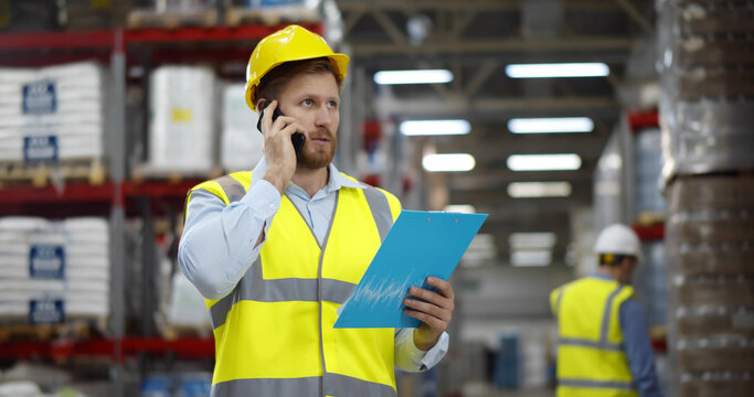 Male worker looking at clipboard while talking on mobile phone in warehouse.