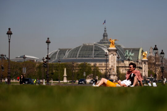 People enjoy a sunny and warm weather in Paris