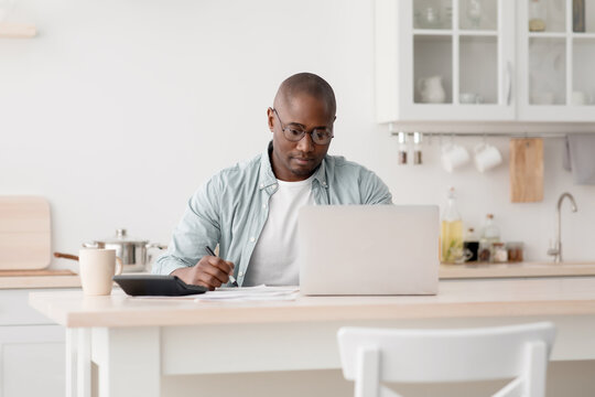 Budget planning concept. Pensive african american man calculating taxes and using laptop computer, sitting in kitchen