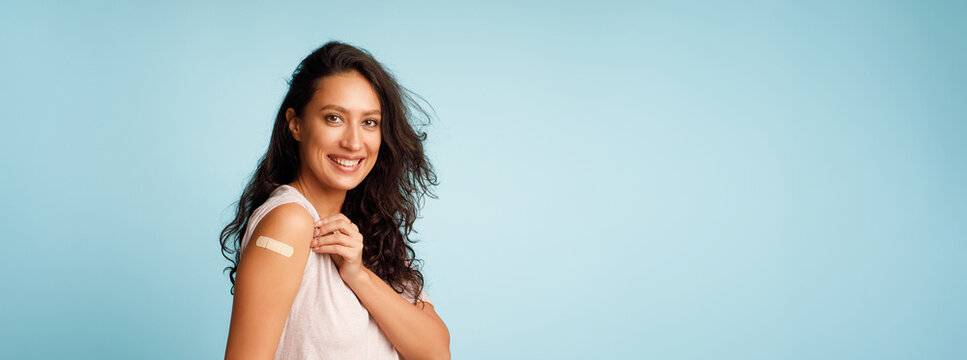 Vaccinated Woman Showing Arm After Covid-19 Vaccine Injection, Blue Background
