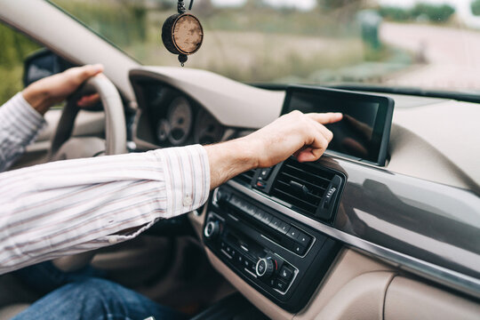 Modern car, man's hand reaches for the screen in the car to turn on the navigator
