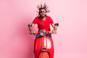 Portrait of handsome cheery dreamy guy riding moped having fun wind blowing spending summer...