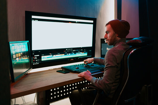 Attractive Male Video Editor Works with Footage or Video on His Personal Computer, he Works in Creative Office Studio or home. Neon lights