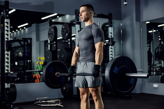 A close-up portrait of a male athlete in a grey fitness t-shirt and shorts. He focused his mind on the best lifting ever in the indoor sports center. Power of the body, physical strong
