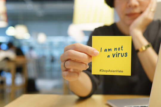 """Stop asian hate hashtag, support Asian americans communities, stop hate crimes campaign. An Asian woman hold a post it note """"I am not a virus"""" Against racism, Campaign, Awareness, Victim, Copy space."""