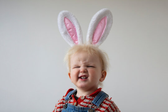 A cute toddler wearing easter bunny ears making a silly smiling face