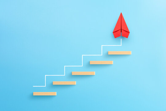 Wooden block stacking as step stair with red paper plane on blue background, Ladder of success in business growth concept, copy space